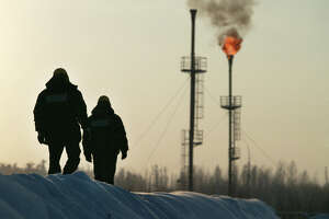 Two workers walk near a gas flare-off at the Yukos owned Mamontovskoye oil-field in the Khanty-Mansy region of the Russian Federation, Friday, December 17, 2004. Russia's state-owned OAO Rosneft said it will take over the main production unit of OAO Yukos Oil Co., the exporter of 11 percent of the nation's petroleum. Photographer: Dmitry Beliakov/Bloomberg News.