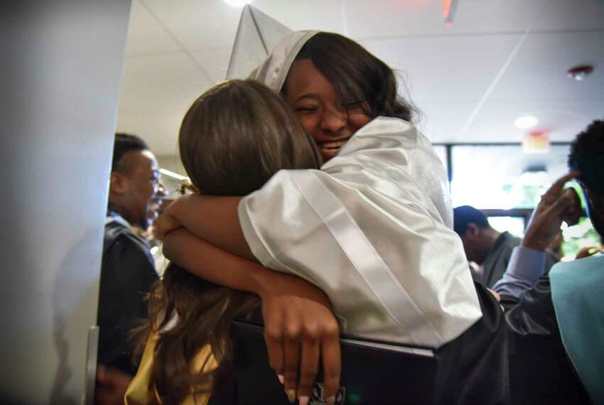 Teacher Taylor Schneider and graduate Ki'miah Sheffey embrace after the Capital Prep Harbor School's second annual commencement on Friday, June 2, 2017 in The Arnold Bernhard Arts Center on the University of Bridgeport campus.