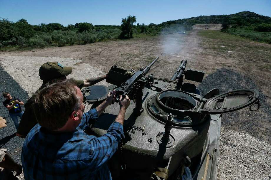 DriveTanks.com cadre Glenn Fleming, left, helps Scott Jones fire the M2 .50 BMG machine gun on the Sherman Easy 8 tank during an Allies and Axis all-day experience at Ox Ranch Wednesday, May 24, 2017 in Uvalde. At the ranch, people can drive and shoot the main canon of vintage WWII-era tanks and fire a variety of machine guns, artillery and other heavy guns. Photo: Michael Ciaglo, Houston Chronicle / Michael Ciaglo