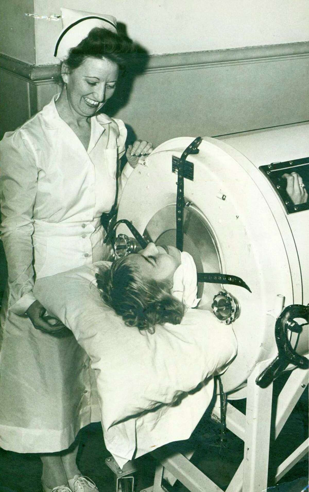 Della Barron, 17-year-old polio patient, spent nearly two weeks in one of the Robert B. Green Hospital's iron lungs in 1948. At her side is Supervisor Josephine Ricks. The iron lung helped victims of the potentially deadly virus breathe.
