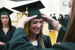Dow's Lauren McLean helps Caroline Milholland adjust her cap while waiting in the gym before commencement on Friday.
