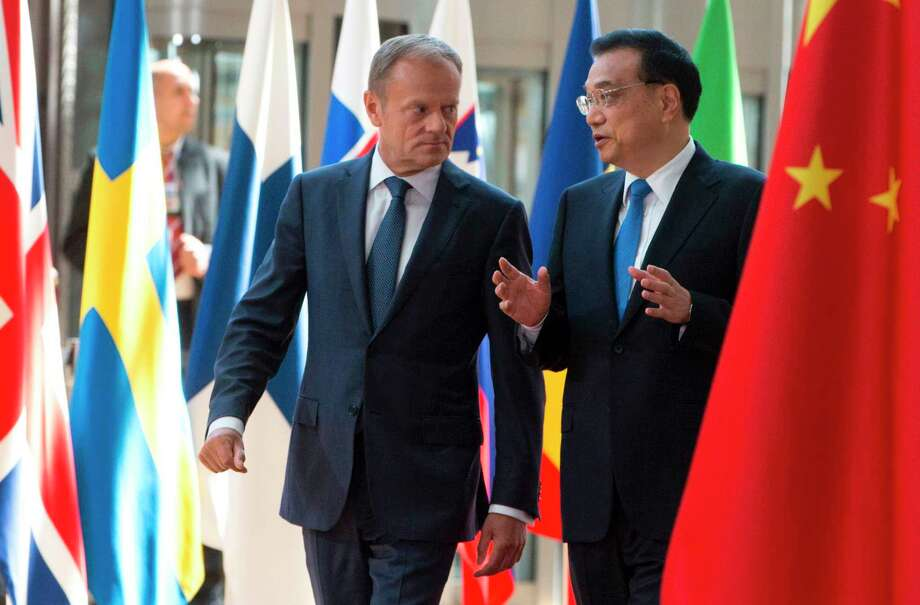 European Council President Donald Tusk walks with Chinese Prime Minister Li Keqiang before an EU summit Friday in Brussels, where European and Chinese officials signed a raft of agreements binding themselves together. Photo: VIRGINIA MAYO, Stringer / AFP