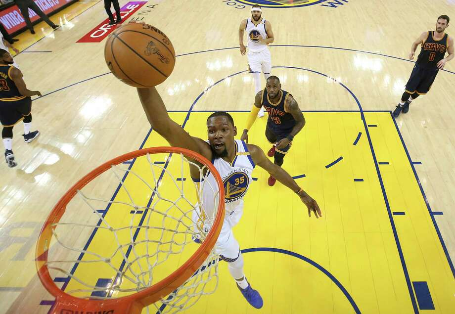 Golden State Warriors forward Kevin Durant (35) dunks in front of Cleveland Cavaliers forward LeBron James during the first half of Game 1 of basketball's NBA Finals in Oakland, Calif., Thursday, June 1, 2017. (Ezra Shaw/Pool Photo via AP) Photo: Ezra Shaw, POOL / Pool Getty Images North America