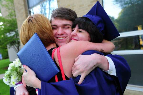 Graduates Isaac Bjerklie, center, and Isabella Manzo, right, get a hug from a relative after Notre Dame of Fairfield's Class of 2017 Commencement Exercises in Fairfield, Conn., on Friday June 2, 2017.