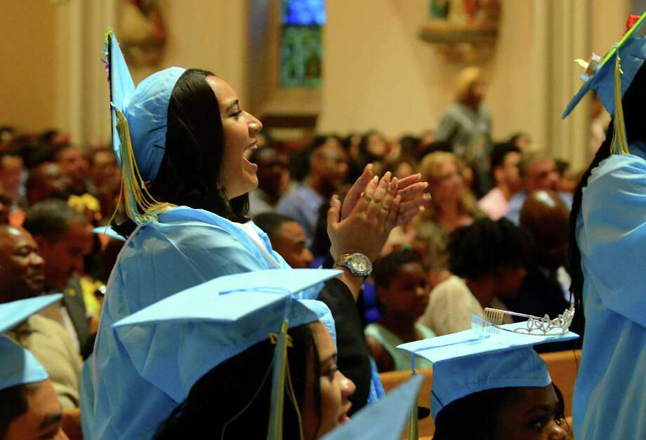 Cynthia Moyano cheers for a fellow graduate during Kolbe Cathedral's Class of 2017 Commencement at St. Augustine Cathedral in Bridgeport on Thursday. Photo: Christian Abraham / Hearst Connecticut Media / Connecticut Post