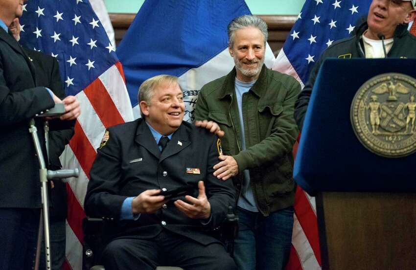 FILE- In this Jan. 9, 2016 file photo, comedian Jon Stewart, right, pats the shoulders of retired FDNY firefighter and Sept. 11 first responder Ray Pfeifer after Pfeifer was given the key to the city at New York's City Hall. Stewart fought back tears Friday, June 2, 2017, during Pfeifer's funeral, as he described his friendship with the retired New York City firefighter who worked in the rescue effort following the Sept. 11 terror attacks. (AP Photo/Craig Ruttle, File) ORG XMIT: NYR101