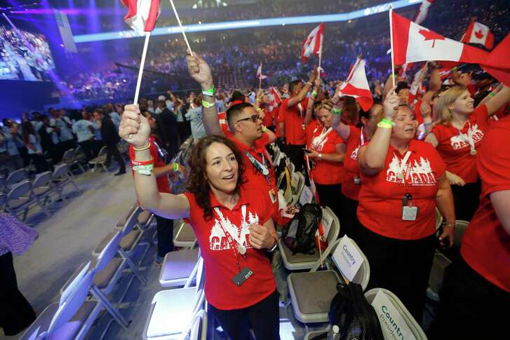 Walmart associates from Canada do a cheer Friday before the Walmart shareholders meeting in Fayetteville, Ark. The big gathering is part pep rally, part music concert, and only briefly a business meeting.