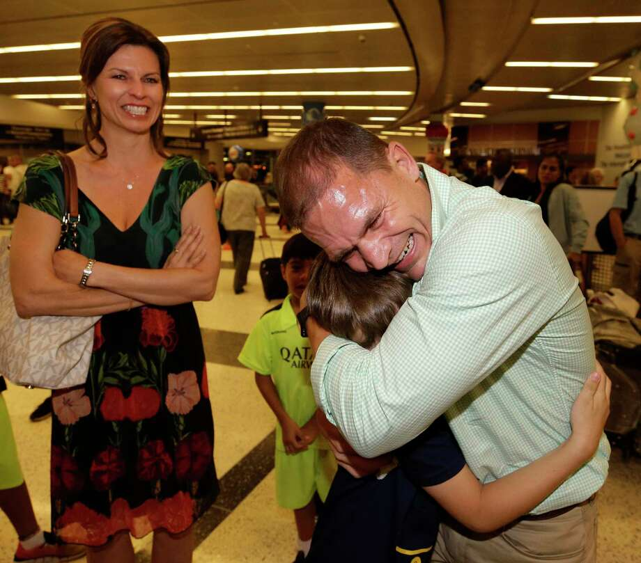 Stacy Davis, left, watches as her husband, Larry Davis, hugs family friend Eichten Beedle, 9, as he is greeted Friday by well-wishers at George Bush Intercontinental Airport after being acquitted on narcotics trafficking charges in the Dominican Republic. Photo: Melissa Phillip, Staff / © 2017 Houston Chronicle