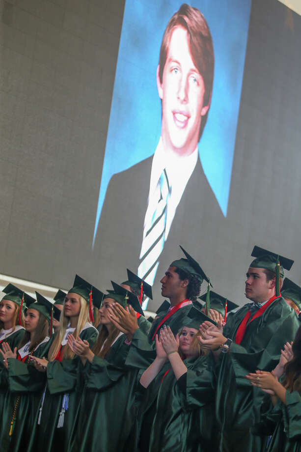 Graduates stand and applaud in honor of The Woodlands senior Grant Milton, pictured on the screen, during The Woodlands High School commencement ceremony on Friday, June 2, 2017, at The Cynthia Woods Mitchell Pavilion. Photo: Michael Minasi, Staff Photographer / © 2017 Houston Chronicle