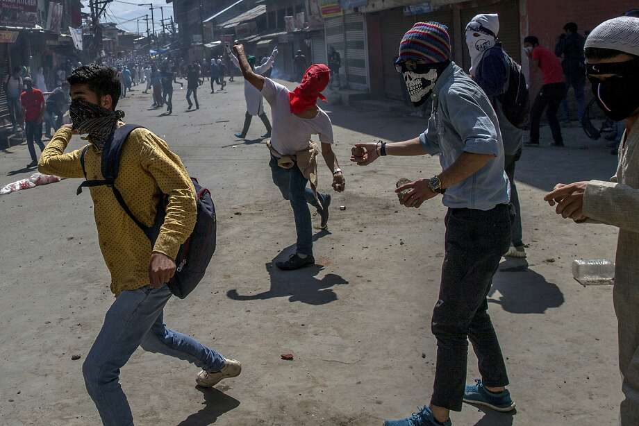 Kashmiri protesters throw rocks and bricks at Indian police officers Friday in Srinagar. Photo: Dar Yasin, Associated Press