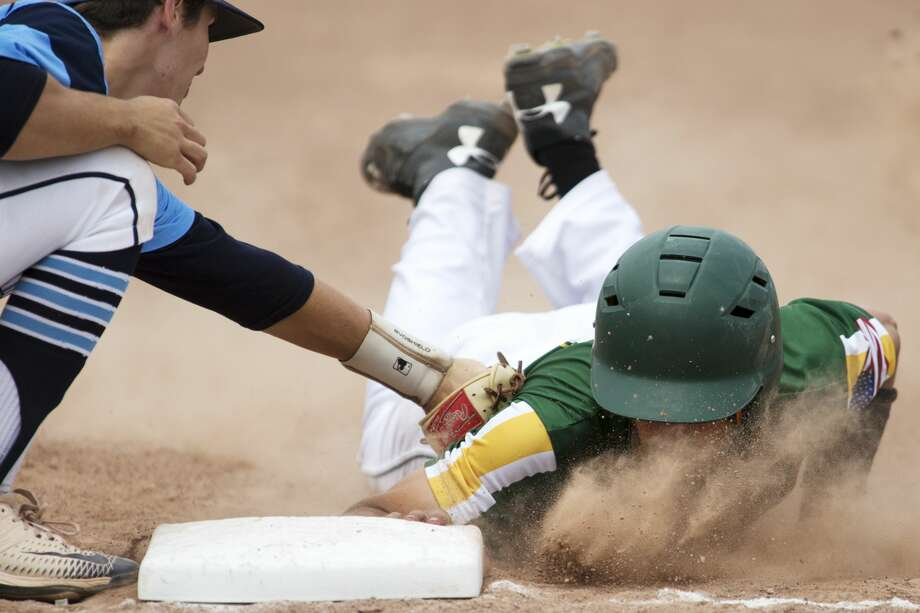 Meridian's Beau Spangler attempts to tag Clare's Cole Keene at first base in the Division 3 quarterfinal game at Meridian on Saturday. Photo: Theophil Syslo