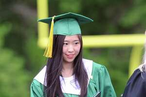 University of Washington-bound she said, Xuanming Da, 19, of Stamford, receives her Trinity Catholic High School dipolma during the commencement at the school in Stamford, Conn., Saturday, June 3, 2017.