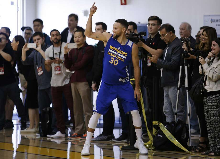 Warriors guard Stephen Curry, surrounded by media members, smiles after hitting a three during a workout at the Warriors' practice facility. Photo: Santiago Mejia, The Chronicle