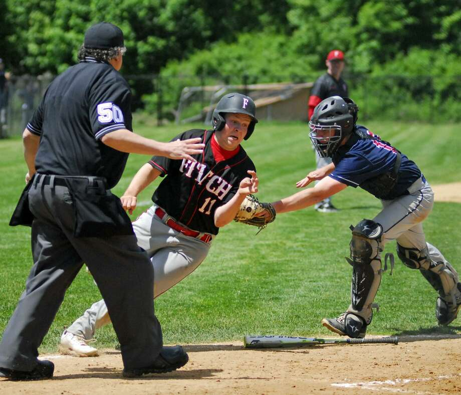 New Fairfield's Jared O'Conner, right, tags out a Fitch runner during Class L quarterfinal action on Saturday. Photo: Ryan Lacey / Hearst Connecticut Media