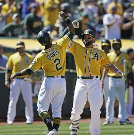 Oakland Athletics' Yonder Alonso, right, celebrates with Khris Davis (2) after hitting a two run home run off Washington Nationals' Jacob Turner in the seventh inning of a baseball game, Saturday, June 3, 2017, in Oakland, Calif. (AP Photo/Ben Margot)