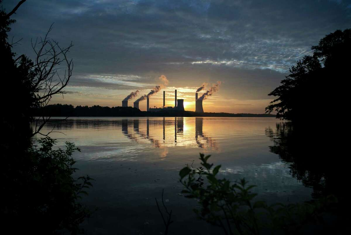 The coal-fired Plant Scherer, one of the nation's top carbon dioxide emitters, stands in the distance in Juliette, Ga., Saturday, June, 3, 2017. U.S. President Donald Trump declared Thursday he was pulling the U.S. from the landmark Paris climate agreement, striking a major blow to worldwide efforts to combat global warming and distancing the country from its closest allies abroad. (AP Photo/Branden Camp)