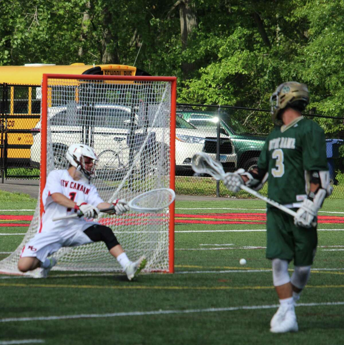 New Canaan goalie Drew Morris knocks away a shot during the Class M lacrosse quarterfinals between New Canaan and Notre Dame-West Haven on Saturday at New Canaan High School. New Canaan defeated Notre Dame-West Haven 16-3.