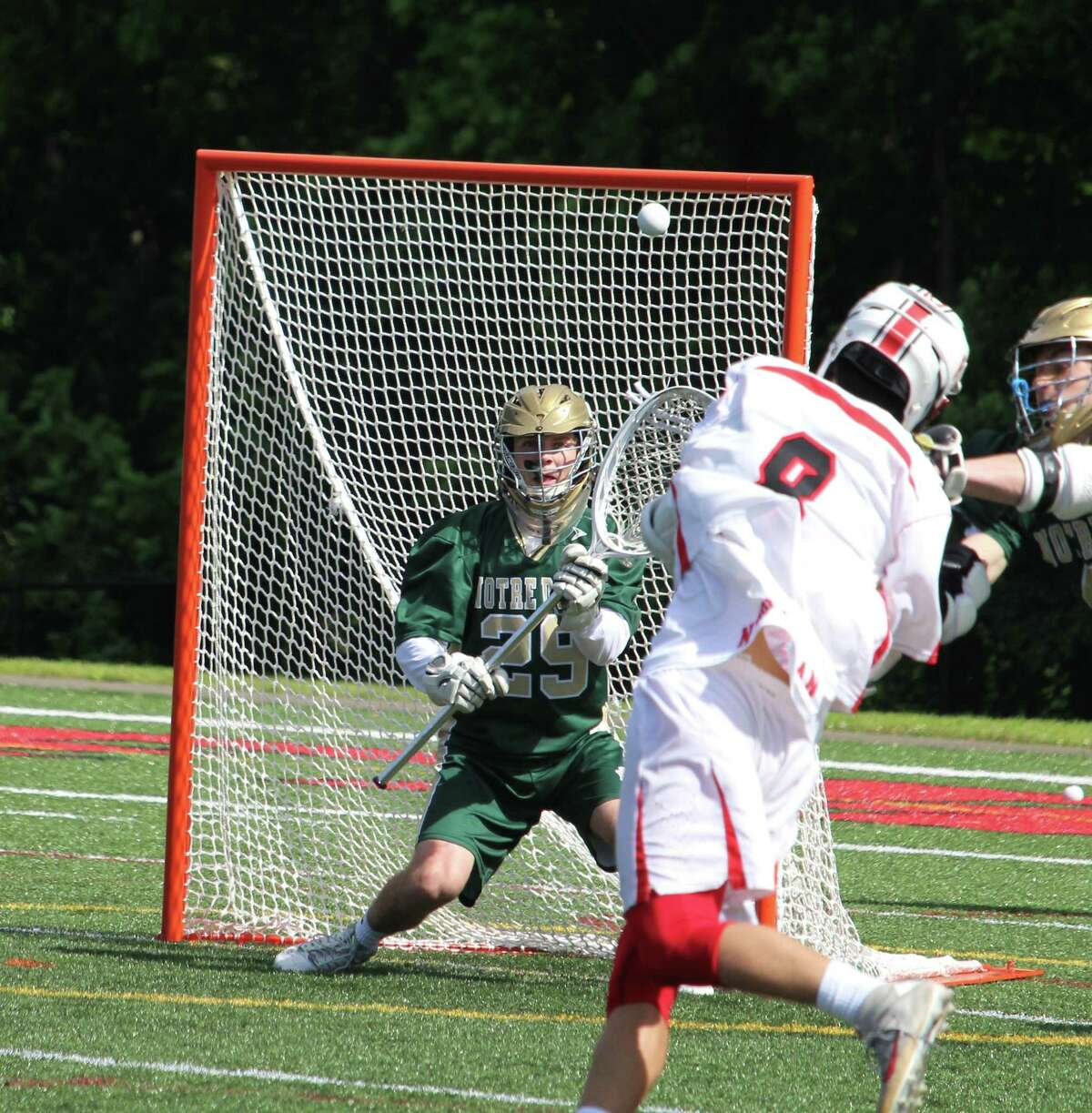 New Canaan's Owen Shin fires a shot that Notre Dame-West Haven goalie Gino Pagliaro saved during the Class M lacrosse quarterfinals between New Canaan and Notre Dame-West Haven on Saturday at New Canaan High School. New Canaan defeated Notre Dame-West Haven 16-3.