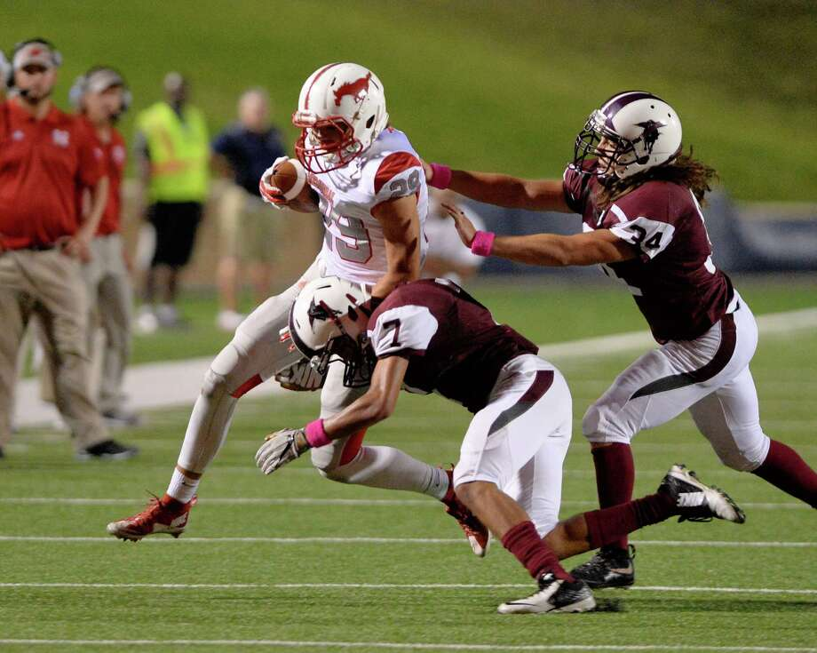 Jack Giammalva (29) of Memorial is tackled by Christian Peguero (7) with assistance from Andrew Rodea (34) in the second half of a high school football game between the Memorial Mustangs and the Northbrook Raiders on Friday October 7, 2016 at Tully Stadium, Houston, TX. Photo: Craig Moseley, Staff / ©2016 Houston Chronicle
