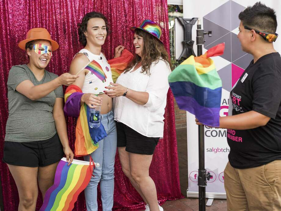 From left, Anastazea Castillo, 17, Joshua Castillo, 20, and their mother Jenny Henley, 45, pose for a picture taken at the LGBT Chamber of Commerce picture booth operated by Jessica Salinas, 32, right, during the third annual Family Pride Fair hosted by the LGBT Chamber of Commerce in San Antonio, Texas on Saturday, June 3, 2017. Photo: Matthew Busch, © Matthew Busch / Matthew Busch For The San Antonio Express-News / © Matthew Busch