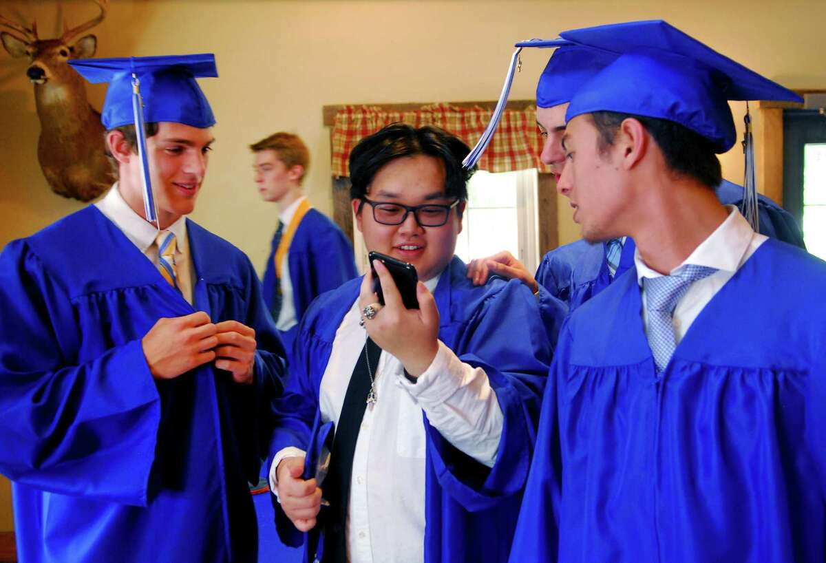 Christian Heritage Academy graduate Khai Chen, center, has a face call on his smart phone with a friend before the start of the academy's 34th annual Commencement Exercises in Trumbull, Conn., on Saturday June 3, 2017.