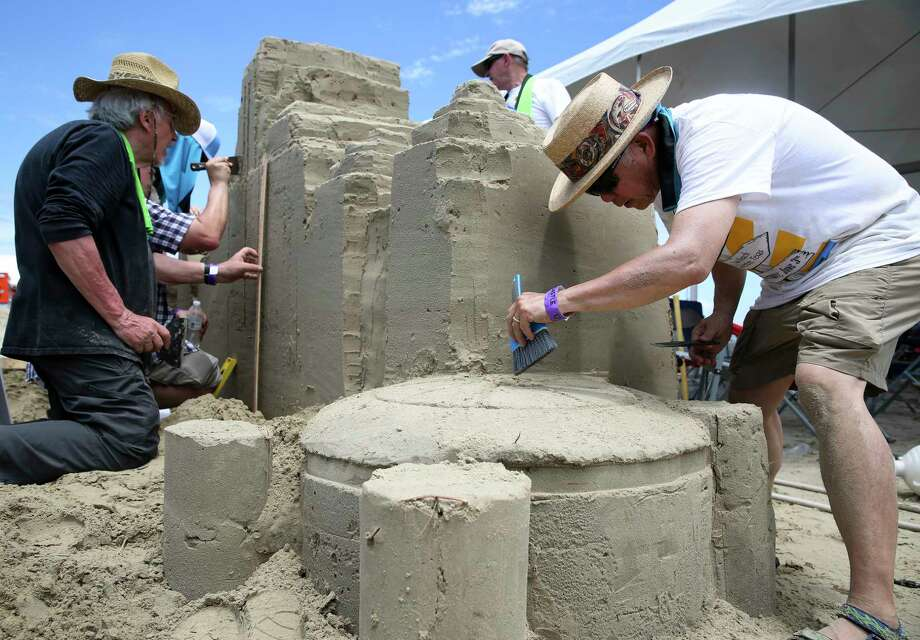 "George Watanabe carefully carves the roof of the Astrodome as his teammates are build the rest of the Houston skyline at the American Institute of Architects' sandcastle competition Saturday at East Beach. The team's concept was called ""Pop-Up Houston."" Photo: Yi-Chin Lee, Staff / © 2017  Houston Chronicle"