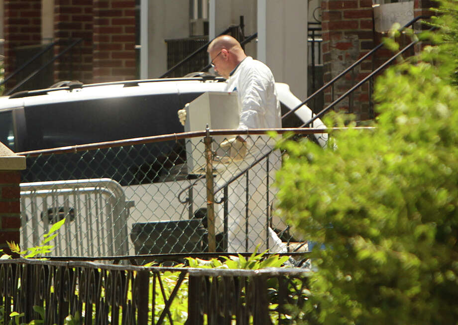 FILE - In this July 14, 2011 file photo, crime scene investigators collect evidence from the home of Levi Aron, who later pleaded guilty to abducting and killing 8-year-old boy Leiby Kletzky, in the Brooklyn borough of New York. On Friday, June 2, 2017, a law enforcement official said Levi's brother, Tzvi Aron, was found dead, his body bound, wrapped in a blanket and stuffed in a basement closet in the same Brooklyn home where detectives uncovered the remains of the boy. (AP Photo/Seth Wenig, File) Photo: Seth Wenig, STF / Copyright 2017 The Associated Press. All rights reserved.