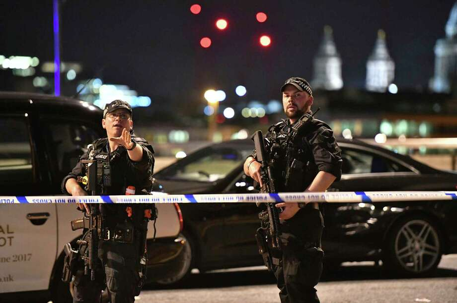 Armed Police officers stand guard on London Bridge in central London Saturday night after witnesses reported a vehicle veering off the road and hitting several pedestrians. Photo: Dominic Lipinski, SUB / PA