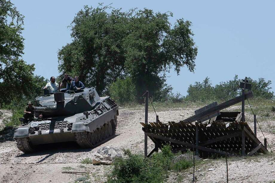DriveTanks.com customers drive the German Leopard 1A4 Tank through the tank course at Ox Ranch Wednesday, May 24, 2017 in Uvalde. At the ranch, people can drive and shoot the main canon of vintage WWII-era tanks and fire a variety of machine guns, artillery and other heavy guns. ( Michael Ciaglo / Houston Chronicle ) Photo: Michael Ciaglo, Staff / Michael Ciaglo