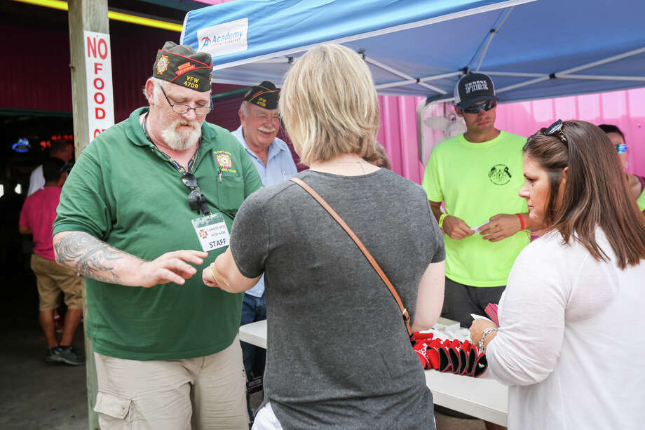 State Deputy Inspector John Tellier, Texas VFW, left, and Conroe firefighter Ryan Vanden Hul, right, sell and attach wristbands to patrons for the 7th Annual Fire up the Bands on Saturday, June 3, 2017, at Papa's On The Lake. Photo: Michael Minasi, Staff Photographer / © 2017 Houston Chronicle