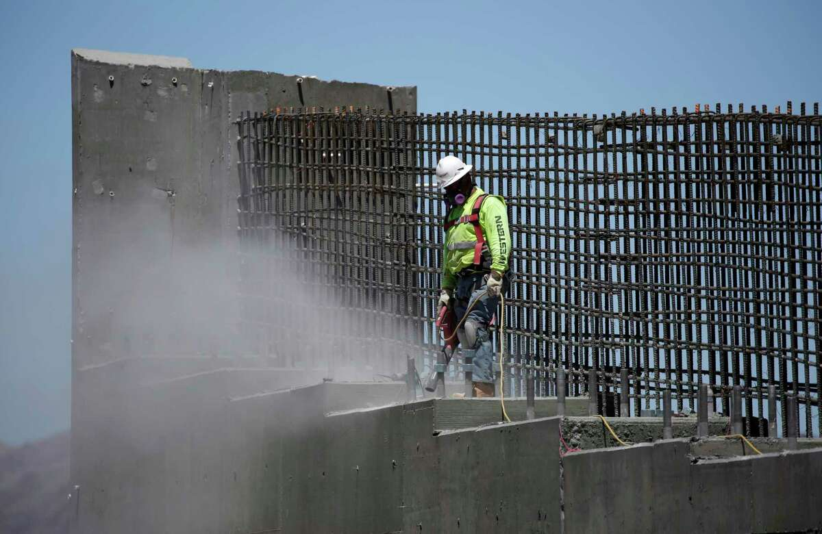 In this May 19, 2017, photo, a man works on the Southern Nevada portion of U.S. Interstate 11 near Boulder City, Nev. President Donald Trump is planning a major push next week to promote a $1 trillion rebuilding of the nation's roads and bridges as his agenda has struggled in Congress and been overshadowed by White House controversies. (AP Photo/John Locher) ORG XMIT: WX109
