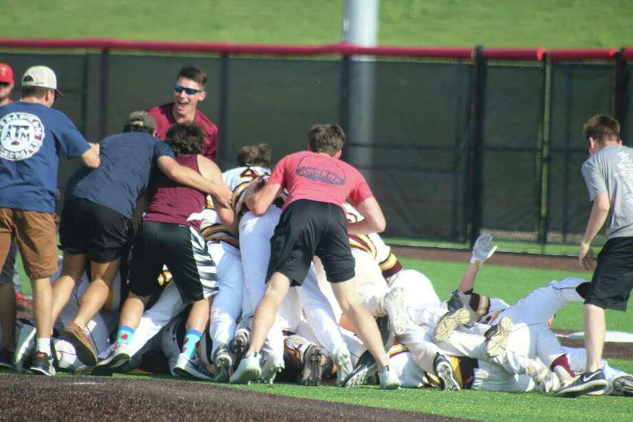 With fans joining the celebration, Deer Park players pile on one another, moments after winning with a walk-off walk. Photo: Robert Avery