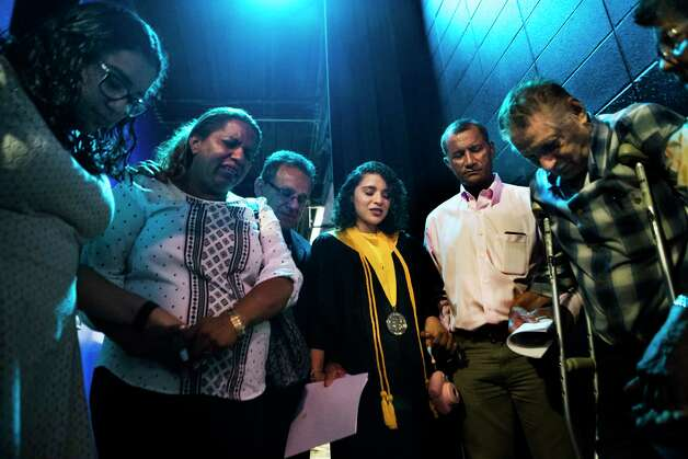 Karen Rodriguez, center, 18, leads her family in prayer after she received her high school diploma during the Cristo Rey Jesuit College Preparatory School of Houston, Saturday, June 3, 2017, in Houston. Photo: Marie D. De Jesus, Houston Chronicle / © 2017 Houston Chronicle