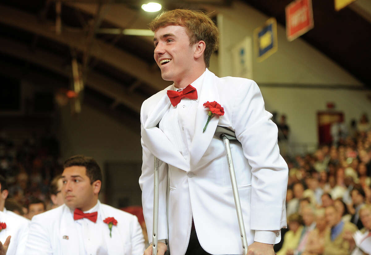 Graduate and Senior Class President Kevin P. Gallagher, Jr. walks on crutches to receive an award during Fairfield Prep's 75th Commencement Exercises at Fairfield University's Alumni Hall in Fairfield, Conn. on Sunday, June 4, 2017