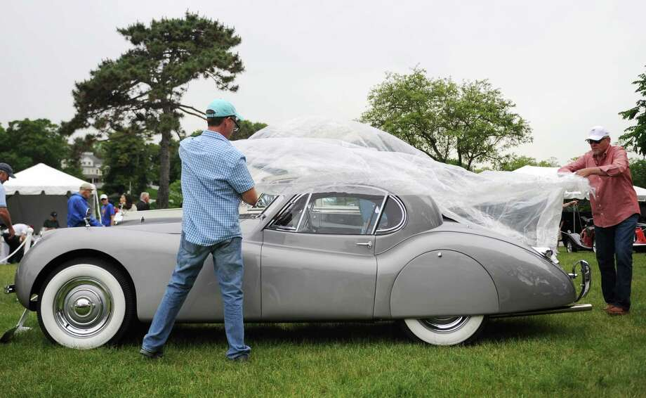 Todd Ressler, left, of Woodbridge, and Kerry Washay, of Torrington, put a cover on a 1954 Jaguar XK120 FHC as rain begins to fall on day two of the 22nd Greenwich Concours d'Elegance car show at Roger Sherman Baldwin Park in Greenwich, Conn. Sunday, June 4, 2017. The Sunday show featured imported cars including more than 20 Bugattis from the American Bugatti Club as well as racecars from the Lime Rock Historic Festival. Photo: Tyler Sizemore / Hearst Connecticut Media / Greenwich Time