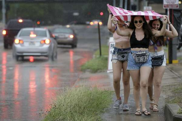 Three women take shelter under their American flag during the evacuation of Eleanor Tinsely Park on Sunday, June 6, 2017 during the annual Free Press Summer Fest. For the past four years, rain has delayed, transferred or canceled the festival for safety reasons.