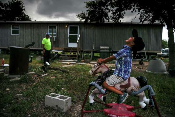 Tayson Penny, 5, rocks on a toy horse as his grandfather watches Tuesday, May 23, 2017 in Tilden, the county seat of McMullen County. McMullen County, a county of only about 800 residents, had the highest average gross income in the country in 2015. ( Michael Ciaglo / Houston Chronicle )