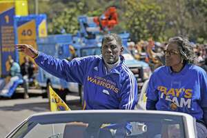 Warriors great Al Attles waves to the crowd on Lakeside Drive as the parade passes by on Friday. The Golden State Warriors celebrated their first NBA Championship in 40 years with a parade through Oakland, Calif.,  on Friday, June 19, 2015.