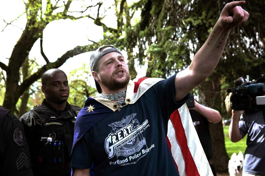 FILE - In this April 29, 2017, file photo provided by John Rudoff, Jeremy Joseph Christian, right, talks during a Patriot Prayer organized by a pro-Trump group in Portland, Ore. Christian, the man accused of stabbing two commuters to death who tried to stop him from hurling anti-Muslim insults at young women on a light-rail train came from a stable family and was a rambunctious teenager who spiraled out of control as he entered his teenage years, according to court records and acquaintances.(John Rudoff via AP, File) Photo: John Rudoff, HONS / Copyright © 2017 John Rudoff, All Rights Reserved. johnrudoff@yahoo.com +1-503-680-3388