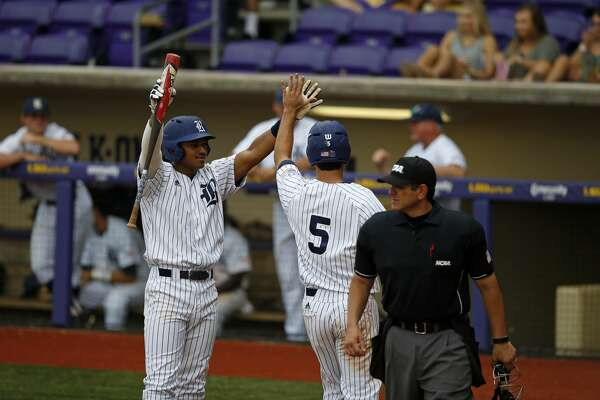 Rice's Charlie Warren (5) celebrates at the dugout after scoring on an RBI by Ford Proctor in the fourth inning of an NCAA college baseball tournament regional game against Southeastern Louisiana in Baton Rouge, La., Sunday, June 4, 2017. Rice won 9-5. (AP Photo/Gerald Herbert)