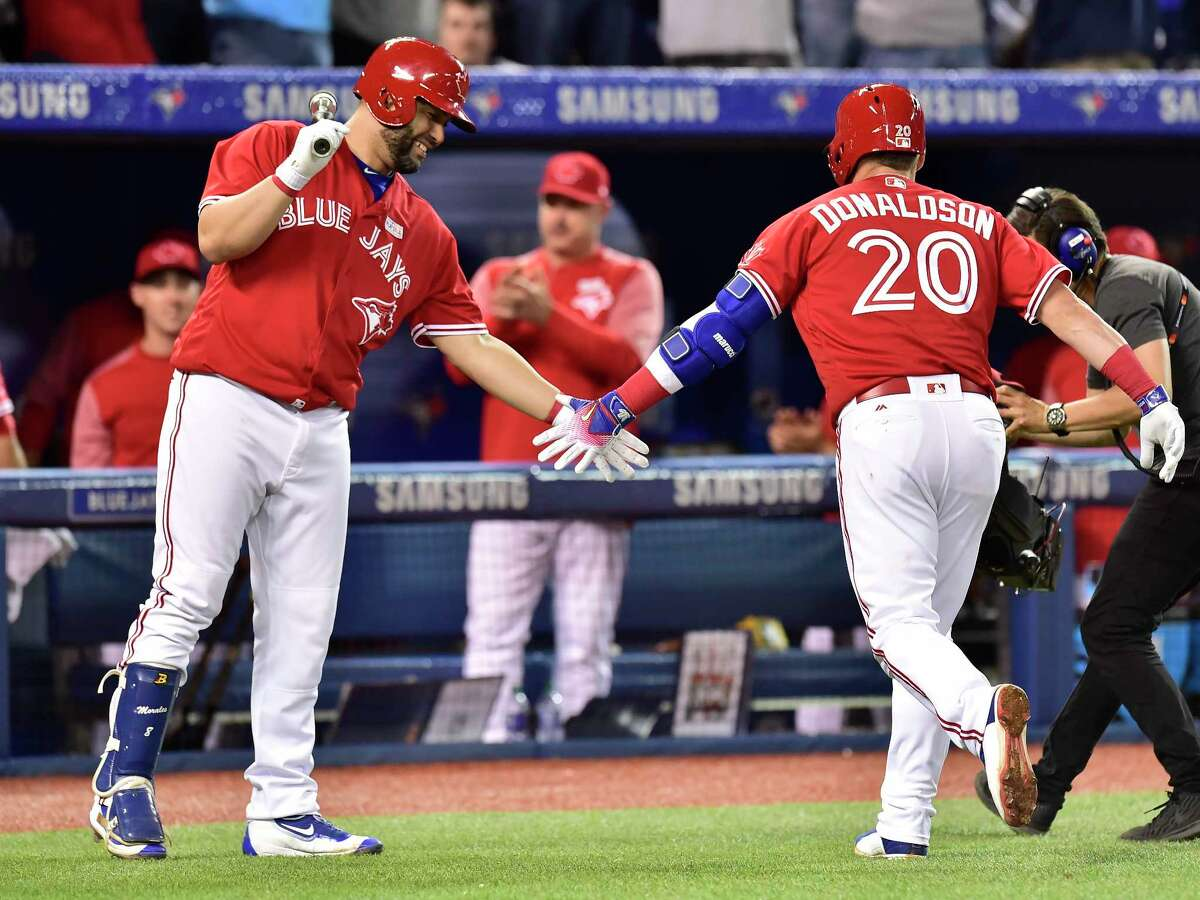 Toronto Blue Jays third baseman Josh Donaldson, right, is congratulated by teammate Kendrys Morales after hitting a solo home run against the New York Yankees during eighth inning American League baseball action in Toronto, Sunday, June 4, 2017. (Frank Gunn/The Canadian Press via AP) ORG XMIT: FNG513