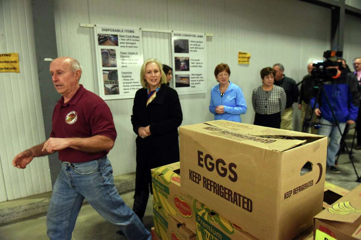 Mark Quandt, left, Executive Director of the food bank gives U.S. Senator Kirsten Gillibrand, center, joined by Albany Mayor Kathy Sheehan, Troy Mayor Patrick Madden, Colonie Supervisor Paula Mahan a tour before they volunteer at the Regional Food Bank of Northeastern New York on Friday Dec. 2, 2016 in Colonie, N.Y. (Michael P. Farrell/Times Union)