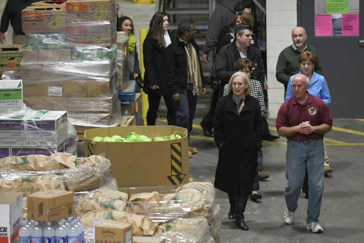 Mark Quandt, right, Executive Director of the food bank gives U.S. Senator Kirsten Gillibrand, left, joined by Albany Mayor Kathy Sheehan, Troy Mayor Patrick Madden, Colonie Supervisor Paula Mahan a tour before they volunteer at the Regional Food Bank of Northeastern New York on Friday Dec. 2, 2016 in Colonie, N.Y. (Michael P. Farrell/Times Union)