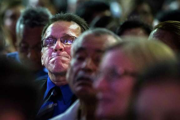 Juan Rodriguez holds back tears at his daughter's high school graduation ceremony Saturday.