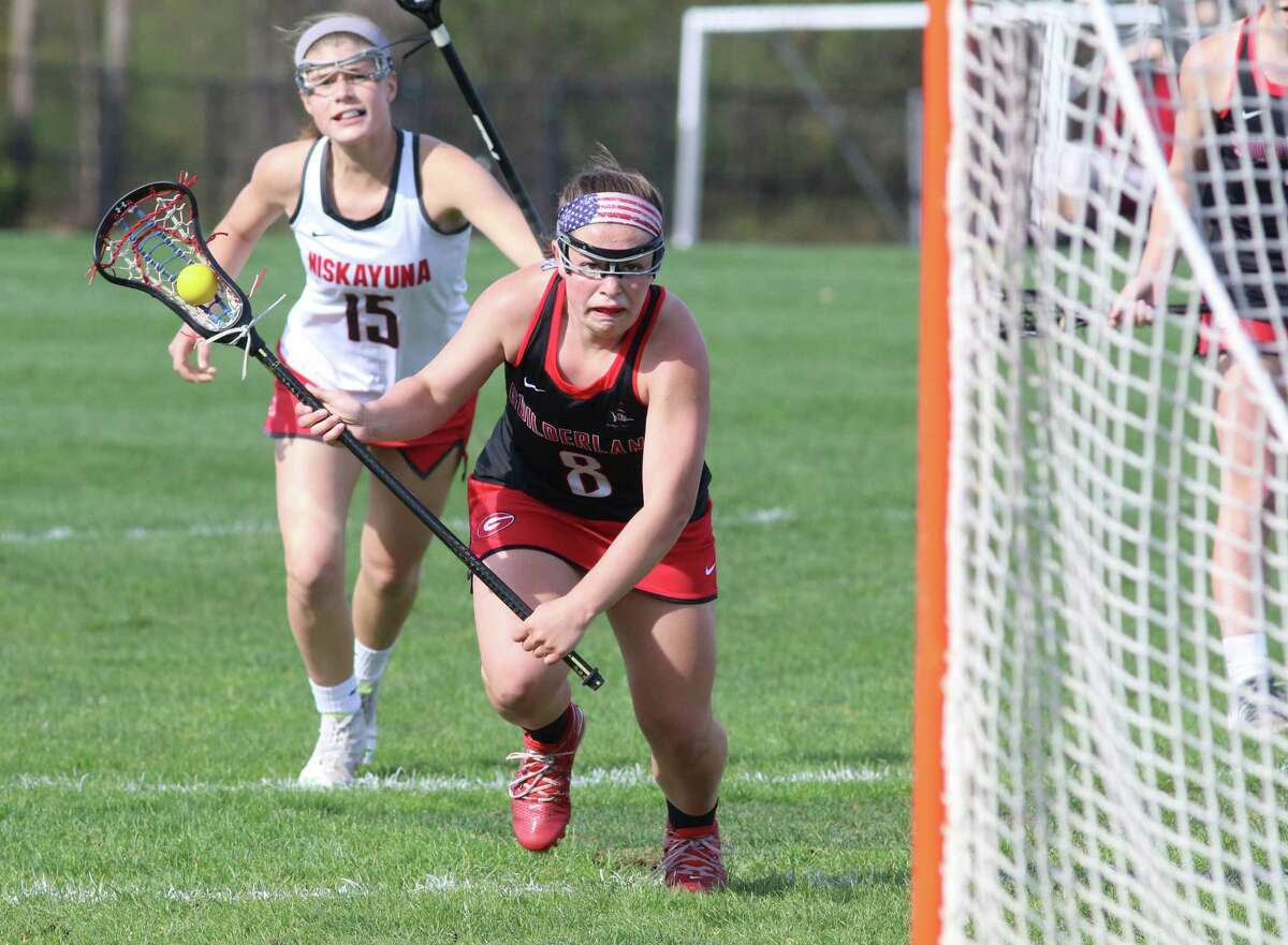 Guilderland's Hayley Kmack charges the net pursued by Nisky's Nora Molino during Thursday's Suburban Council girls' lacrosse matchp at Niskayuna High School. (Ed Burke-Special to The Times Union)