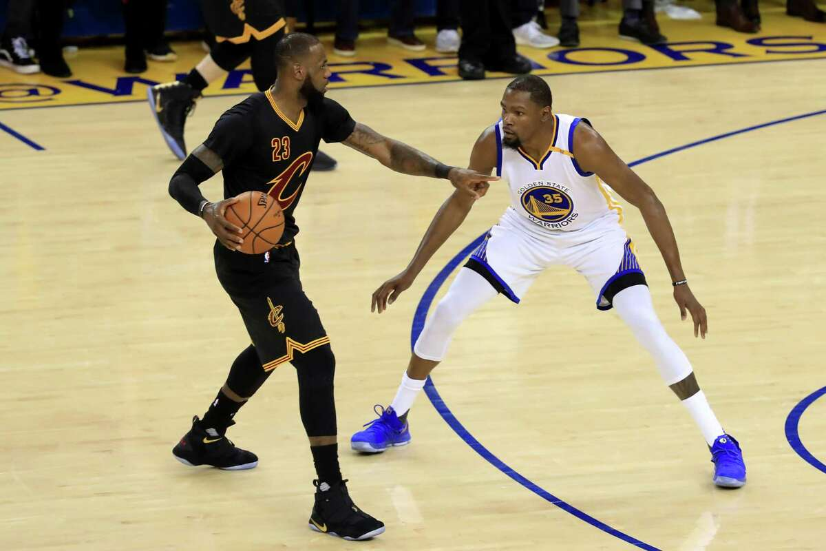 OAKLAND, CA - JUNE 04: LeBron James #23 of the Cleveland Cavaliers is defended by Kevin Durant #35 of the Golden State Warriors during the first half in Game 2 of the 2017 NBA Finals at ORACLE Arena on June 4, 2017 in Oakland, California. NOTE TO USER: User expressly acknowledges and agrees that, by downloading and or using this photograph, User is consenting to the terms and conditions of the Getty Images License Agreement. (Photo by Ronald Martinez/Getty Images) ORG XMIT: 700056190