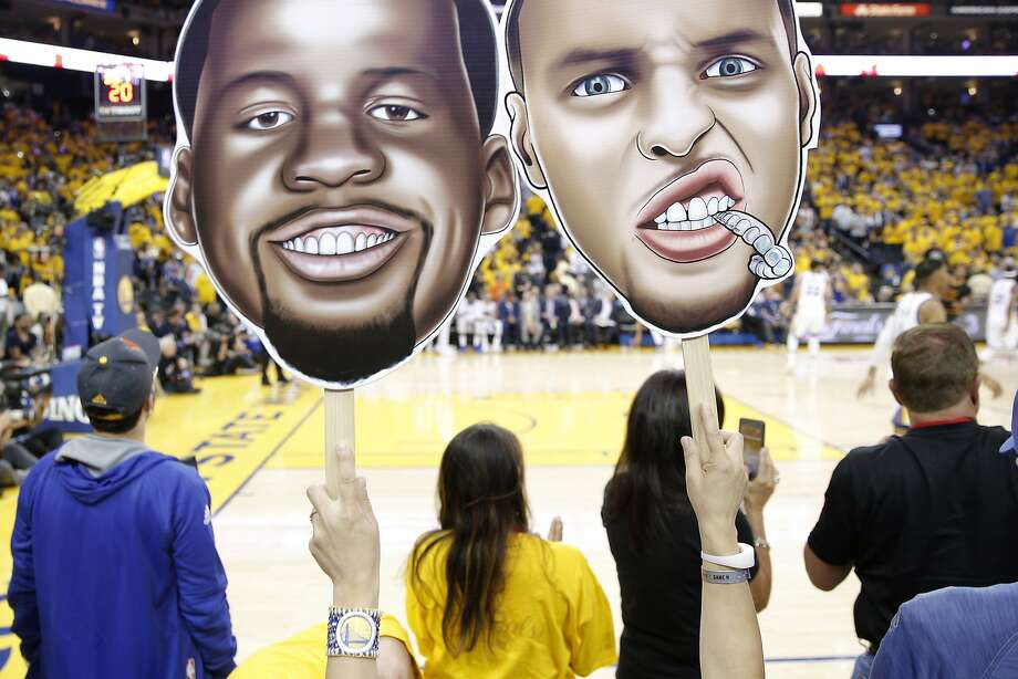 A fan holds cutouts of Golden State Warriors forward Draymond Green (23) and Golden State Warriors guard Stephen Curry (30) during Game 2 of the NBA Finals between the Golden State Warriors and the Cleveland Cavaliers on Sunday, June 4, 2017, at Oracle Arena in Oakland, Calif. Photo: Santiago Mejia, The Chronicle