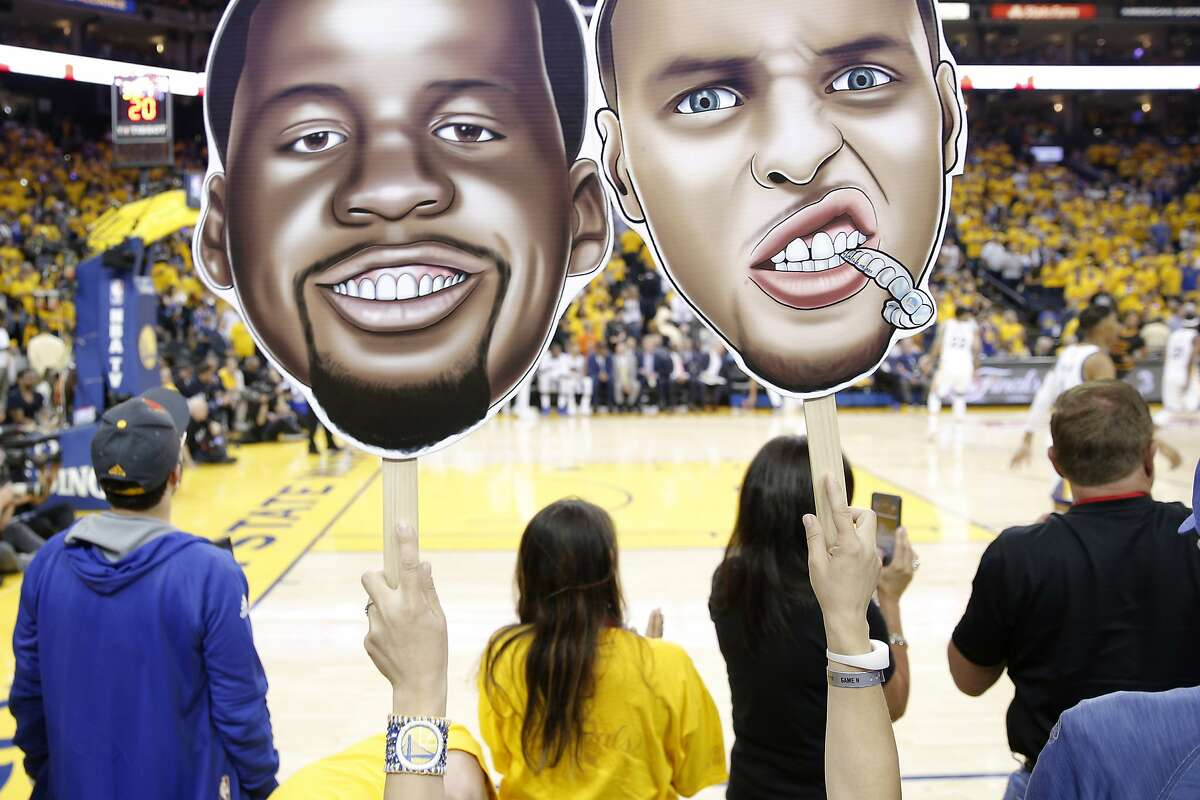 A fan holds cutouts of Golden State Warriors forward Draymond Green (23) and Golden State Warriors guard Stephen Curry (30) during Game 2 of the NBA Finals between the Golden State Warriors and the Cleveland Cavaliers on Sunday, June 4, 2017, at Oracle Arena in Oakland, Calif.