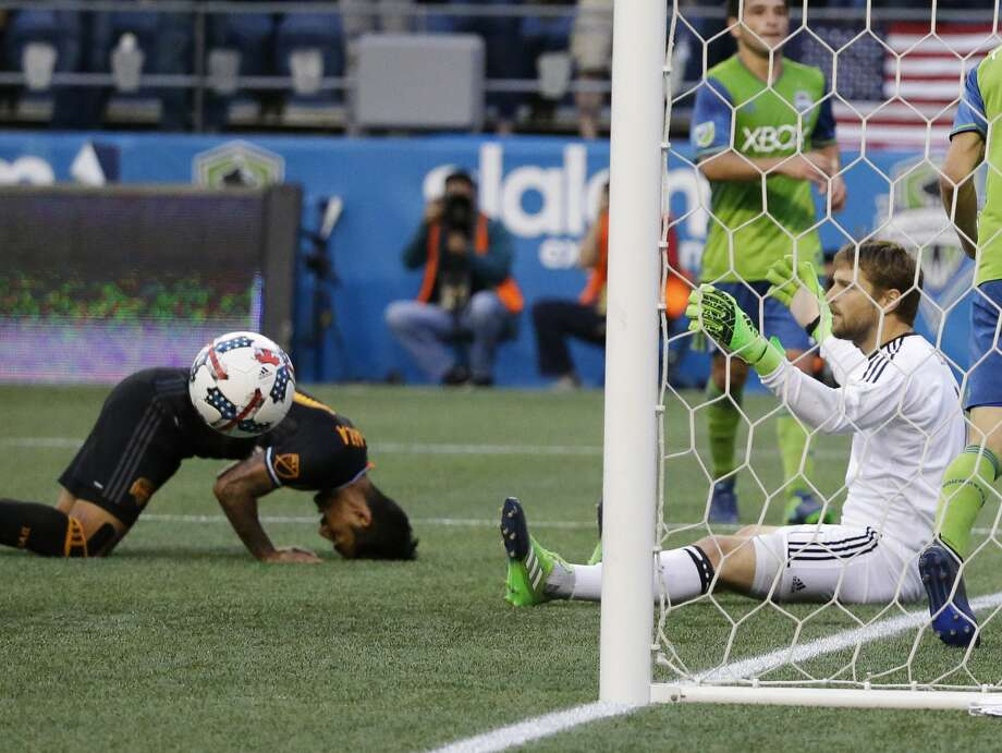 Houston Dynamo goalkeeper Tyler Deric, right, sits in the goal as the ball bounces out and A. J. DeLaGarza reacts at left after Seattle Sounders' Will Bruin scored with a header in the second half of an MLS soccer match, Sunday, June 4, 2017, in Seattle. The Sounders won 1-0. (AP Photo/Ted S. Warren) Photo: Ted S. Warren/Associated Press