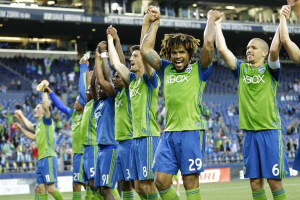 Seattle Sounders players, including Osvaldo Alonso, right, and Roman Torres (29) celebrate after they beat the Houston Dynamo 1-0 in an MLS soccer match, Sunday, June 4, 2017, in Seattle. (AP Photo/Ted S. Warren)